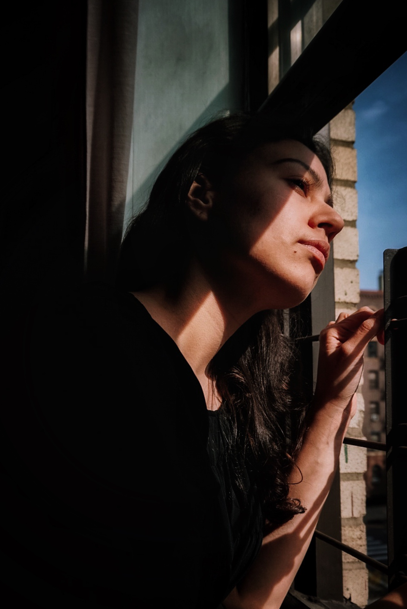 nyc girl looking out from window during covid19